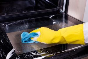 Close up of hand with yellow protective gloves cleaning oven door glass