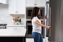 A Neli customer awaiting instructions from a technician while standing in front of her fridge.