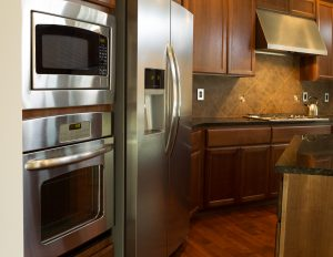Closeup photo of stainless steel appliances in modern residential kitchen with stone counter tops and cherry wood cabinets with hardwood floors