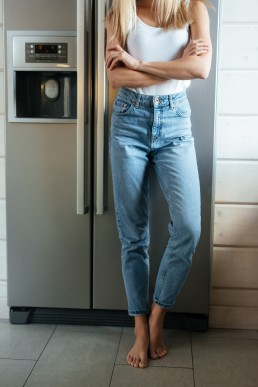 Vertical image of woman standing near the fridge